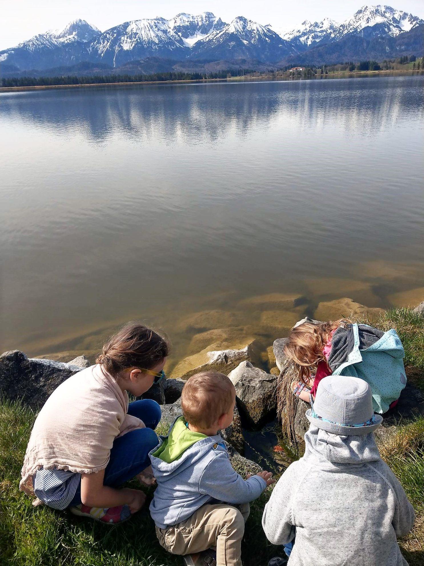 Der Blick auf die Berge, während die Kinder im Wasser nach Süßwassermuscheln suchen, ist einen Tagesausflug an den Hopfensee wert!