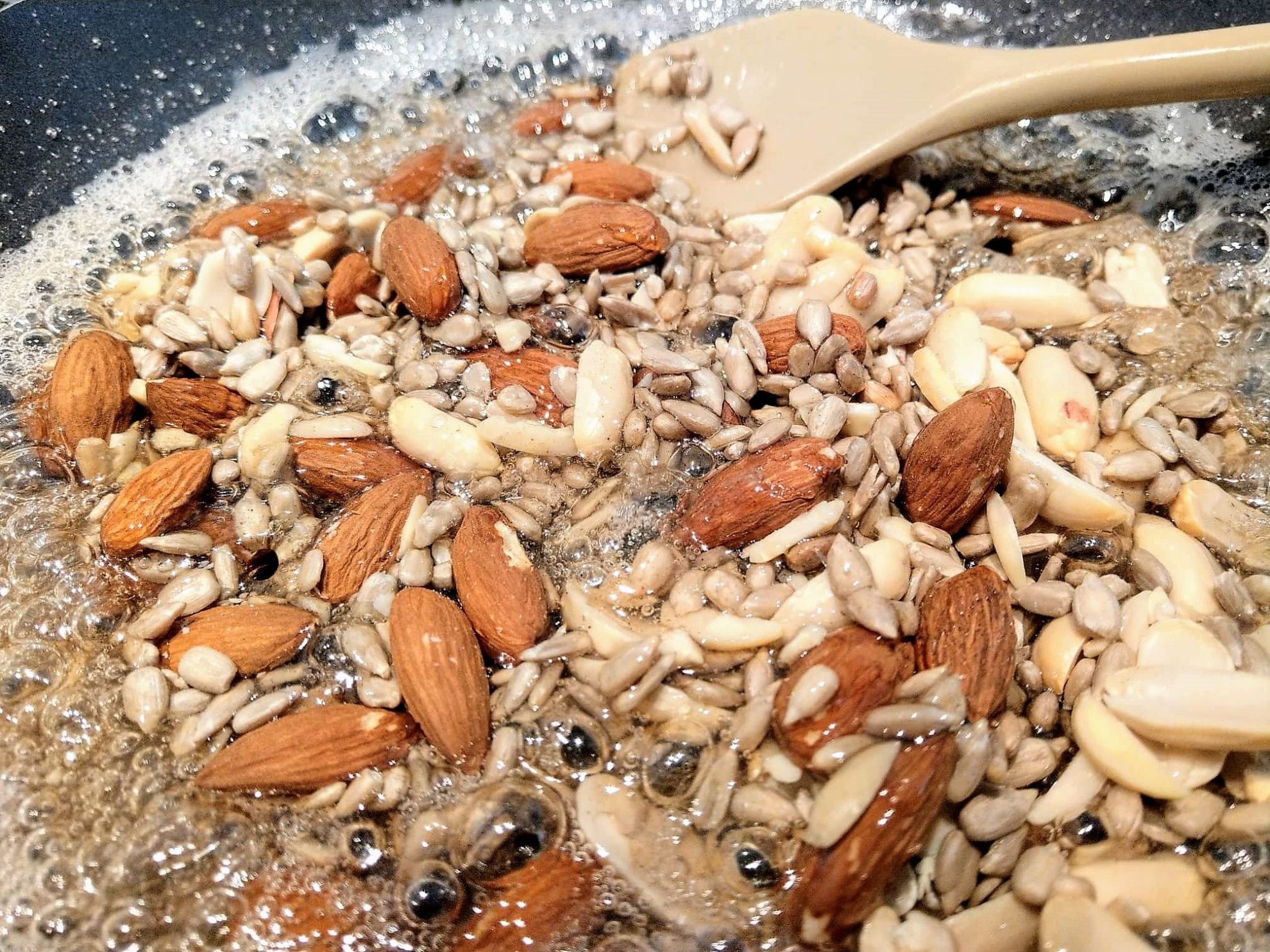 Die Nüsse oder Kerne landen in der Pfanne, sobald das Gemisch aus Zucker und Wasser sich leicht bräunlich verfärbt.