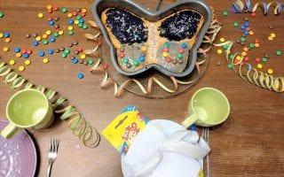 Der Geburtstagstisch ist gedeckt mit einem Schmetterlingskuchen für den großen Tag der Großen