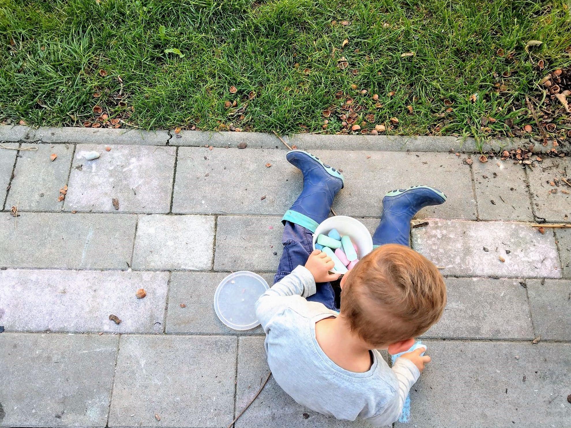 Spielen mit Strassenmalkreide und in Gummistiefeln